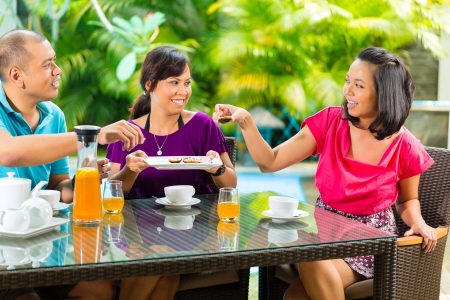 asian couple happy: Asian friends having coffee on the porch in front of a home, in the background a tropical garden