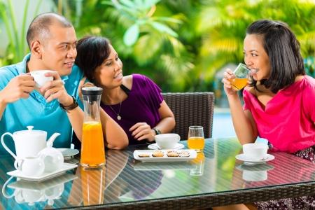 Asian Freunden einen Kaffee auf der Veranda vor einem Hause, im Hintergrund ein tropischer Garten