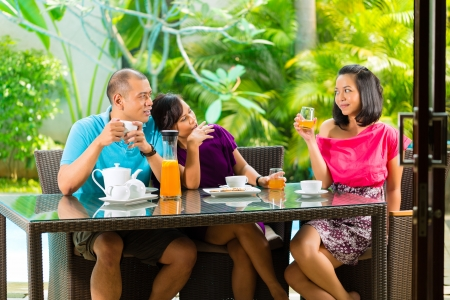 Asian friends having coffee on the porch in front of a home, in the background a tropical garden photo