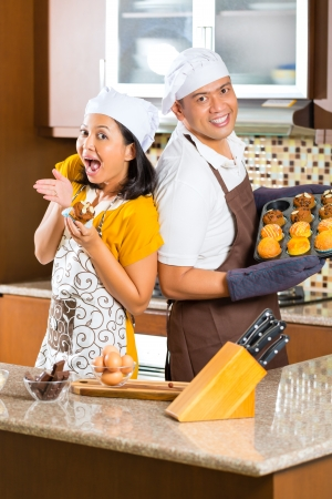 Asian couple, man and woman, presenting homemade cup cake muffins they bake in their kitchen for dessert photo