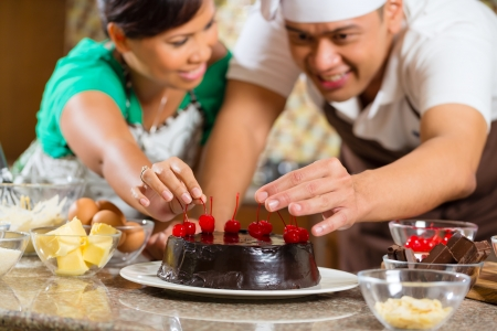 cake decorating: Asian couple baking homemade chocolate cake with cherries  in their kitchen for dessert