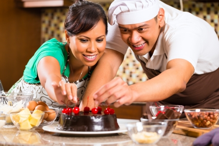 Asian couple baking homemade chocolate cake with cherries  in their kitchen for dessert photo