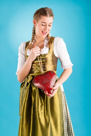 tracht: Young woman in traditional Bavarian clothes - dirndl or tracht with a valentines heart Stock Photo