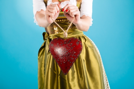 dirndl: Young woman in traditional Bavarian clothes - dirndl or tracht with a valentines heart Stock Photo