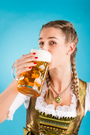 stein: Young woman in traditional Bavarian clothes - dirndl or tracht with a beer stein and beer