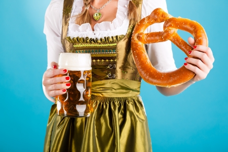 Young woman in traditional Bavarian clothes - dirndl or tracht with a beer stein and beer and pretzel photo