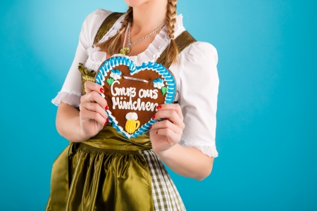 tracht: Young woman in traditional Bavarian clothes - dirndl or tracht with a gingerbread souvenir heart