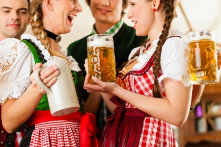steins: Young people in traditional Bavarian Tracht in restaurant or pub with beer and steins