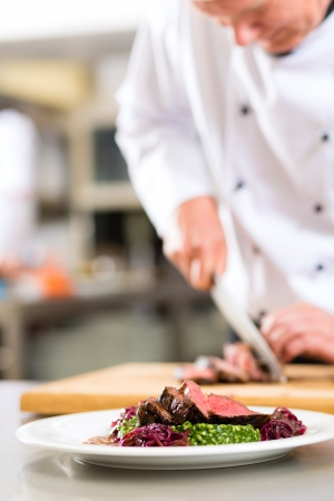 Chef in hotel or restaurant kitchen cooking, he is cutting meat or steak for a dish on plate Stock Photo - 18344837