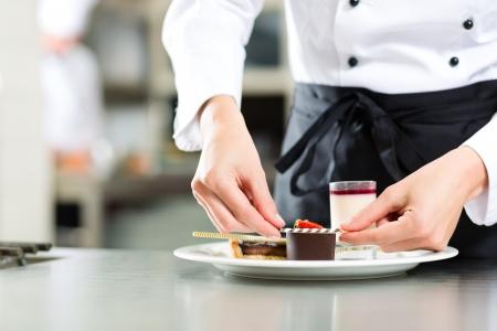 postres: Cocinar, el chef de pasteler�a femenino, en el hotel o cocinar cocina del restaurante, que est� terminando un postre dulce Foto de archivo