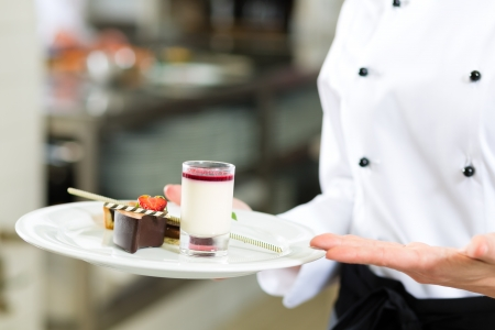 commercial kitchen: Cook, the female pastry chef, in hotel or restaurant kitchen cooking, she is finishing a sweet dessert