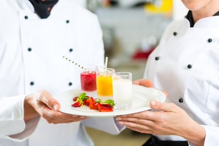 Chef team in restaurant kitchen with dessert working together Stock Photo - 18344895