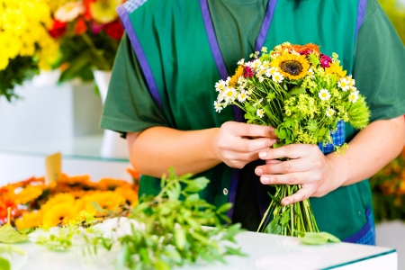 florist shop: Female florist in flower shop or nursery presenting roses preparing a bouquet