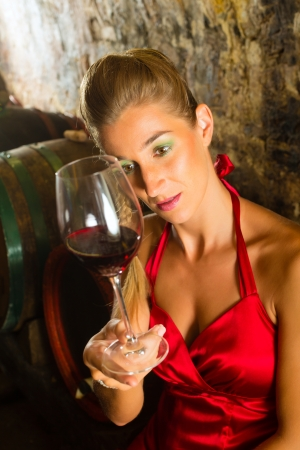Woman looking at wine glass and sitting in wine cellar Stock Photo - 18344680