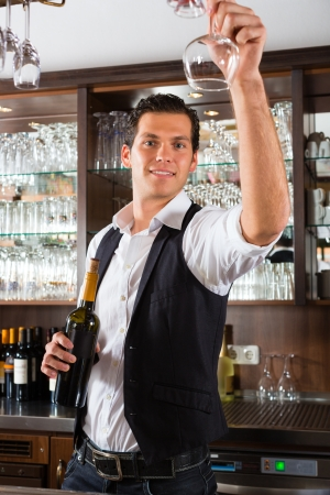 Barman standing behind bar in restaurant reaching for a wineglass photo