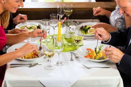 Familie, Mutter und Vater mit erwachsenen Kindern und Tochter oder Sohn im Gesetz-fine dining in schönen Restaurant oder Hotel