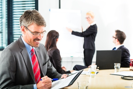 Business - businesspeople have a meeting with presentation in office, they negotiate a contract - Portrait of a businessman Stock Photo - 18344820