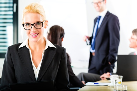 teambuilding: Business - businesspeople have a meeting with presentation in office, they negotiate a contract - Portrait of a businesswoman