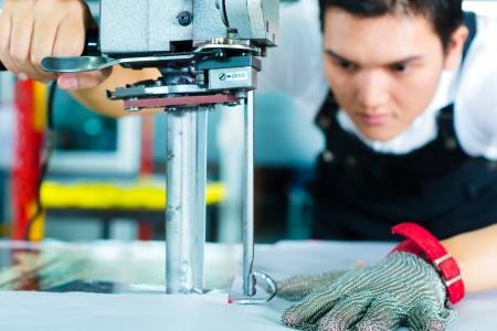 industria tessile: lavoratore con un taglierino - una grande macchina per il taglio di tessuti, in una fabbrica tessile cinese, indossa un guanto catena Archivio Fotografico