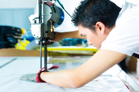garment industry: worker using a cutter - a large machine for cutting fabrics- in a Chinese textile factory, he wears a chain glove Stock Photo