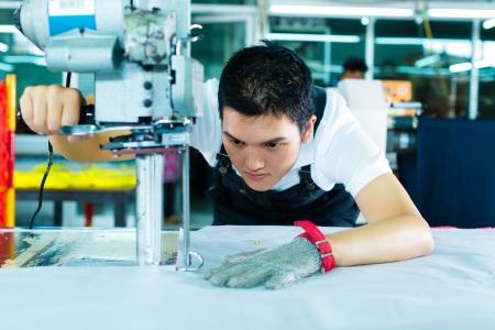 Arbeiter mit einem Cutter - eine große Maschine zum Schneiden von Gewebe in einer chinesischen Textilfabrik, trägt er eine Kette Handschuh