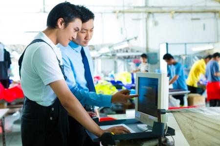 industria tessile: Worker � nuovo assegnato a una macchina in una fabbrica tessile, il caposquadra spiega qualcosa