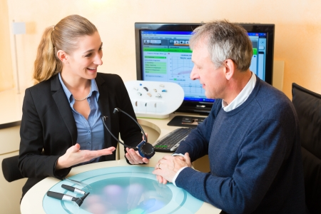 Older man or pensioner with a hearing problem make a hearing test and may need a hearing aid