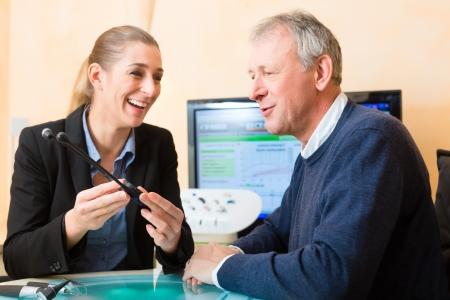 personas escuchando: Hombre mayor o pensionado con un problema auditivo hacer una prueba de audici�n y pueden necesitar un aud�fono