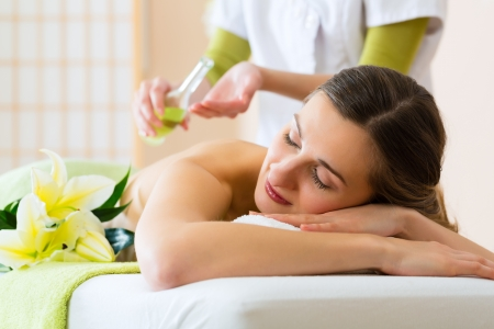Beautiful woman having a wellness back massage and feeling visibly good about it photo