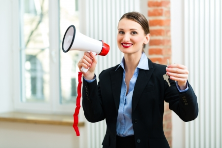 accommodation broker: Young realtor is with keys in an apartment, she makes advertising with a megaphone