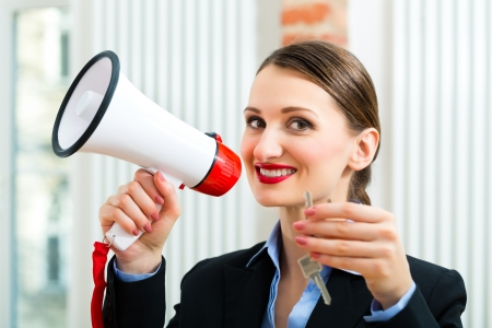 Young realtor is with keys in an apartment, she makes advertising with a megaphone Stock Photo - 18344816