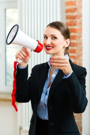 Young realtor is with keys in an apartment, she makes advertising with a megaphone Stock Photo - 18344824