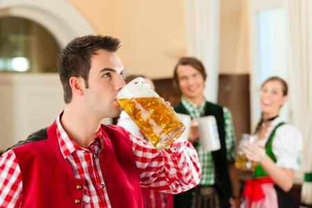 hombre tomando cerveza: La gente joven en Tracht bávaro tradicional en el restaurante o pub, un hombre está de pie con jarra de cerveza en el frente, el grupo en el fondo Foto de archivo