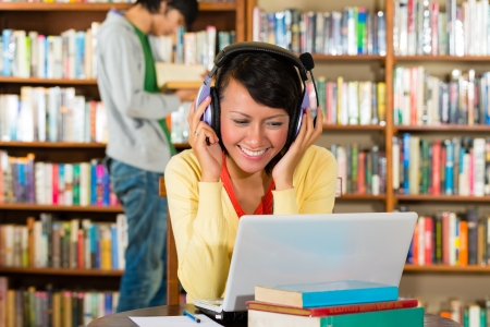library student: Student - Young woman in library with laptop and headphones learning, a male student standing in the Background reads a book