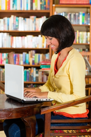 Student - Young woman in a library, writes on laptop learning photo
