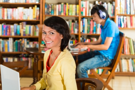 adult indonesia: Students write in library learning on the Laptop - Portrait of a female student Stock Photo