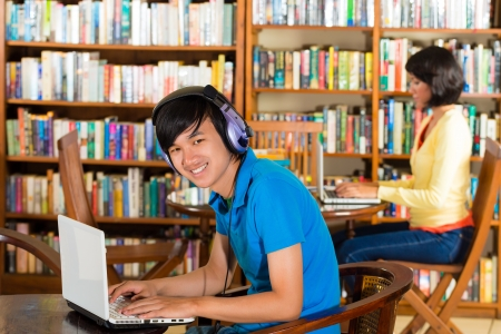 adult indonesia: Students writing in library learning on the Laptop - Portrait of a young man