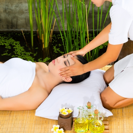 Beautiful Asian woman having a wellness Head massage in a tropical setting and feeling visibly good about it Stock Photo - 18452356