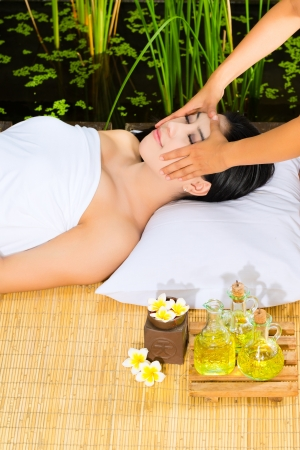 Beautiful Asian woman having a wellness Head massage in a tropical setting and feeling visibly good about it Stock Photo - 18452319