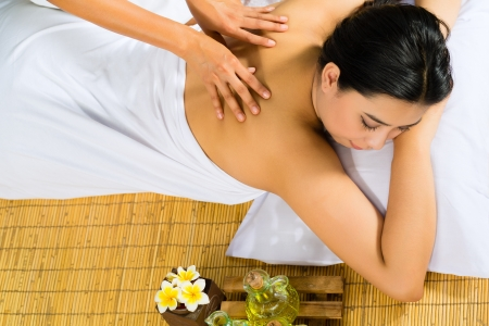 Beautiful Asian woman having a wellness back massage in a tropical setting and feeling visibly good about it Stock Photo - 18451754