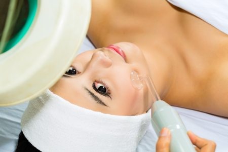 Asian Woman lies in a beauty spa getting a treatment photo