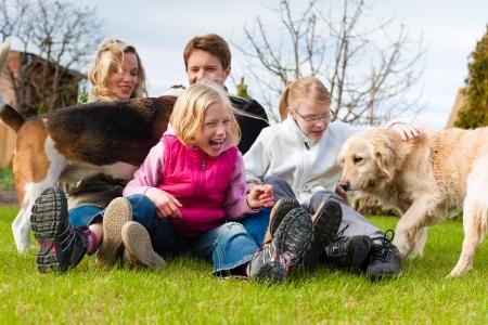Familia, padre, madre y sus hijas, sentadas junto a sus perros en un prado, se ríen y se divierten Foto de archivo