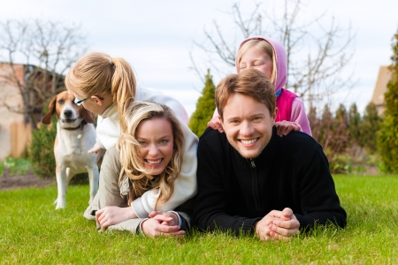 weekend activities: Family, father, mother and daughters, sitting together with their dogs on a meadow, they laugh and have fun