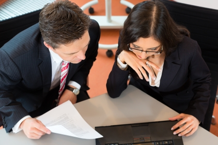 lawyer meeting: Businesspeople sitting at office desk with a document and laptop Stock Photo