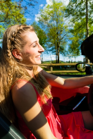 Young beautiful woman  with cabriolet convertible car in summer on a day trip photo