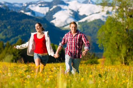 enyoing: Happy couple running on the grass in front of mountain panorama