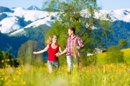 Happy couple running on the grass in front of mountain panorama photo