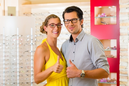 eye glass: Young couple at optician in the store, they looking for glasses