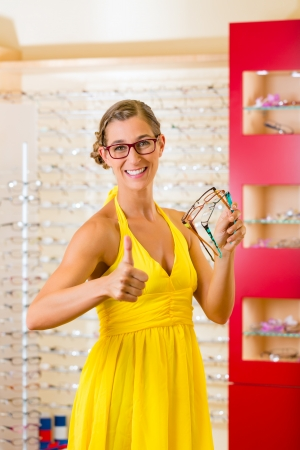 Young woman at optician with glasses, she might be customer or salesperson Stock Photo - 18452410