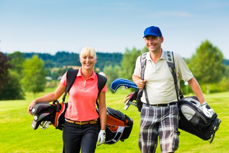Young sportive couple playing golf on a golf course, they walking to the next hole photo